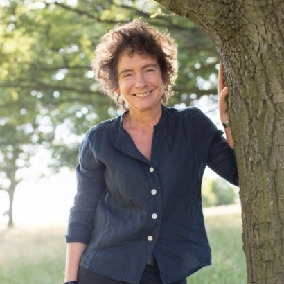 author Jeanette Winterson standing next to a tree