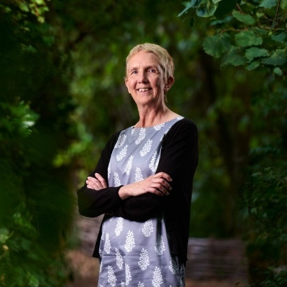 Image of Ann Cleeves stood in a maze of Beech hedges
