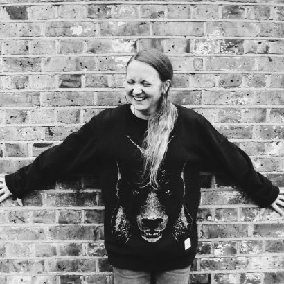 Image of Hollie McNish with her back to a brick wall, laughing