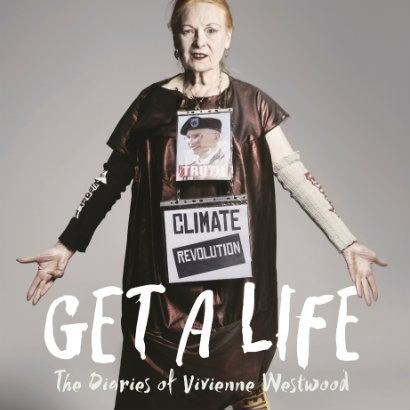 Image of Vivienne Westwood in a long dark smock, with a sign reading 'Climate Revolution' pinned to her front, and her arms outstretched