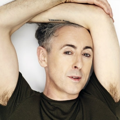 Image of Alan Cumming with both arms crossed above his head, and his armpit hair showing above his t-shirt sleeves
