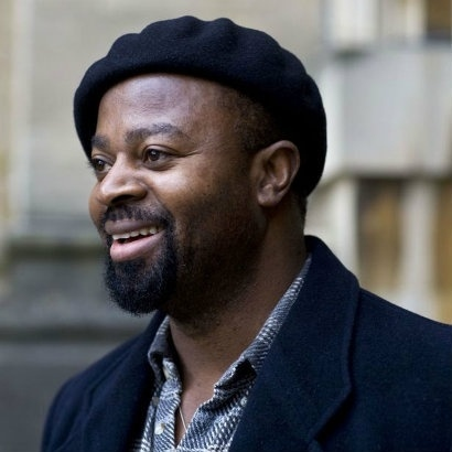 Image of Ben Okri in a black beret smiling at something off camera