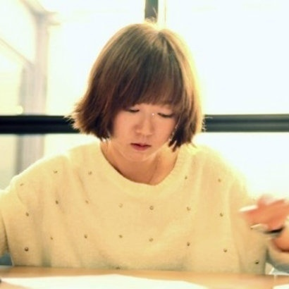 Soft image of Hwang Jung-Eun caught up in reading a sheet of paper on the table in front of her