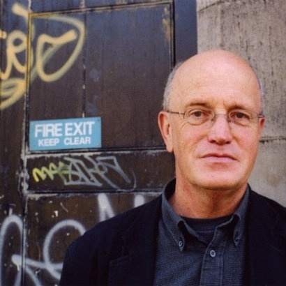 Image of Iain Sinclair standing in front of a graffitied door