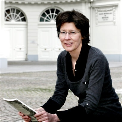 Image of Helen McEwan sat with a book in her hand in a cobbled square, with two white Georgian doorways in the background