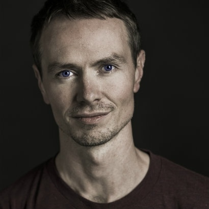 Head and shoulders image of Gavin McCrea with slight stubble and a half-smile