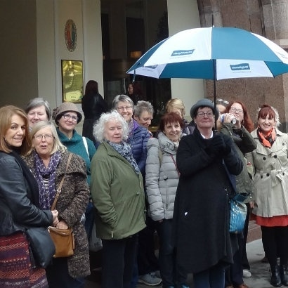 Image of Anne Beswick and a tour group, standing under an umbrella in front of the Midland Hotel