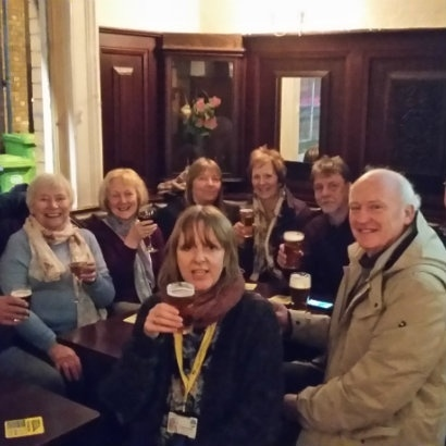 Image of Suzanne Hindle and a tour group enjoying a drink in a pub