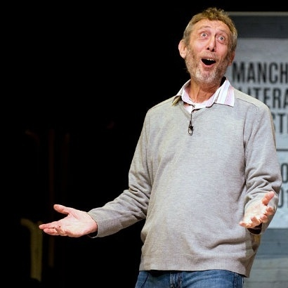 Image of Michael Rosen on stage, looking amused with his hands outstretched