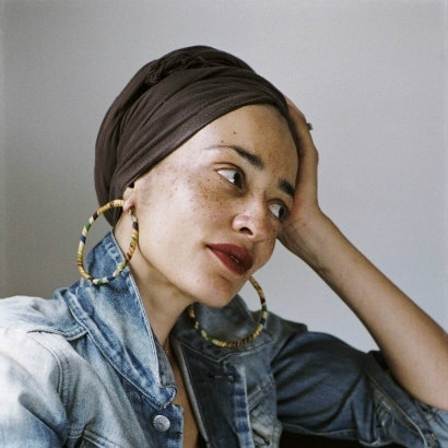 an image of the author Zadie Smith with her hand on her head looking away from the camera