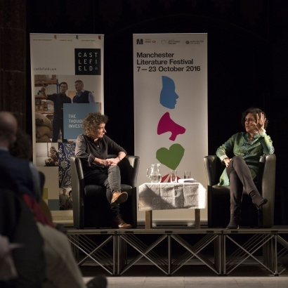 Distant image of Jeanette Winterson and Kamila Shamsie looking at each other on stage