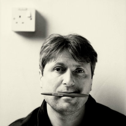 Head and shoulders image of Simon Armitage with a pen in his mouth