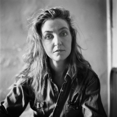 Black and white image of Rebecca Solnit in a dark button-up shirt, looking to camera