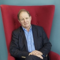 Michael Morurgo sat in a red armchair