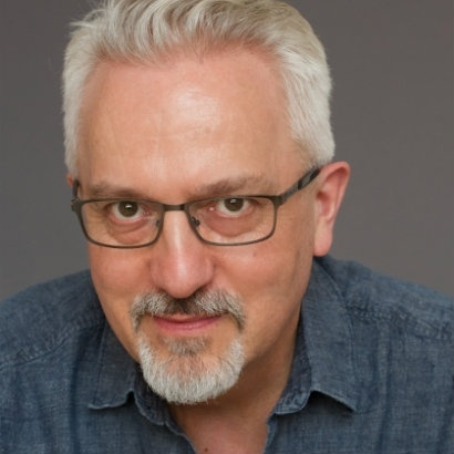 Author Alan Hollinghurst looking slightly amused, with a grey background