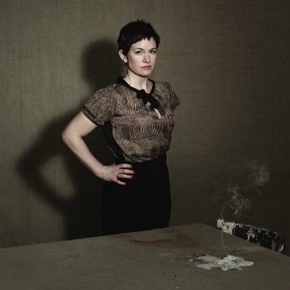 Sarah Hall standing with her hands on her hips in front of a bare wooden table and paint-stained chair
