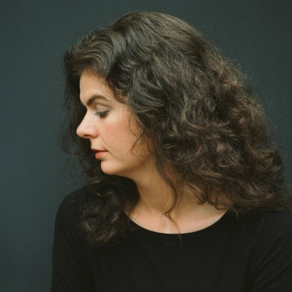 Image of Tara Bergin with her head to the side, with long, curly brown hair