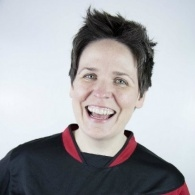 Image of Comedy Club 4 Kids' Kate McCabe in a red and black football shirt, and grinning at the camera