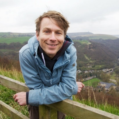 Image of Ben Faulks in a blue cagoule, leaning on a wooden fence in the countryside