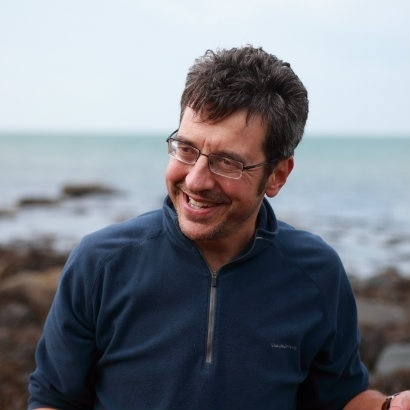 Image of George Monbiot on a rocky seashore, wearing a dark blue fleece