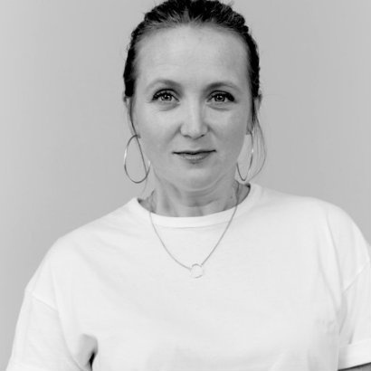 Image of Hollie McNish in a white t-shirt and big hoop earings