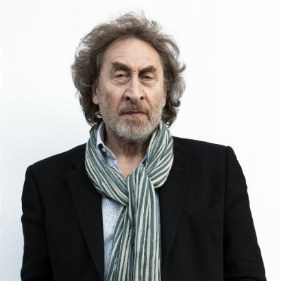 Image of Howard Jacobson with a large grey- and white-striped scarf, frowning slightly at the camera