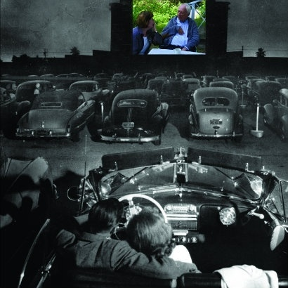 Black and white image of a young couple in a car at an old American drive-in cinema