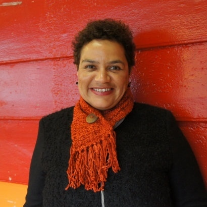 Picture of Jackie Kay, smiling broadly and standing in front of a bright red wooden hut