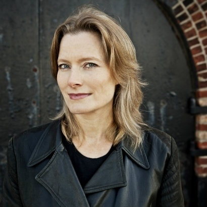 Jennifer Egan in a black leather jacket, standing in front of a brick archway