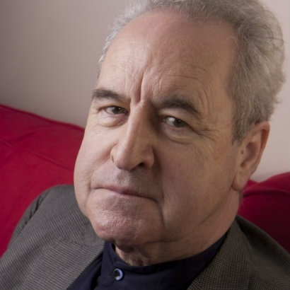 Image of John Banville, looking serious on a red sofa