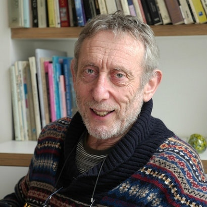 Image of Michael Rosen in a colourful fairisle jumper, sitting in front of book shelves