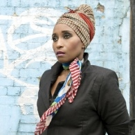Image of Malika Booker in a brown and orange checked head scarf, standing in front of a pale blue, grafitied wall