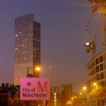 Image of Manchester by night, with the Beetham Tower and a crane in the background
