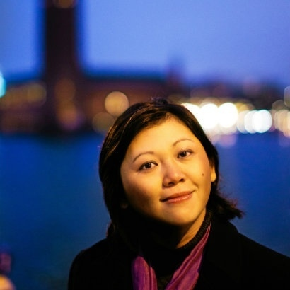 Image of Yiyun Li in a black coat and pink scard, with the hazy lights of a city behind her