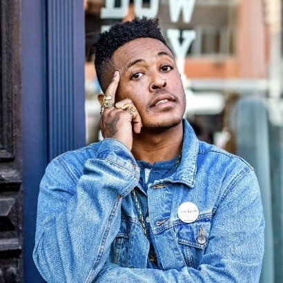 Image of Danez Smith standing in the street in a blue denim jacket