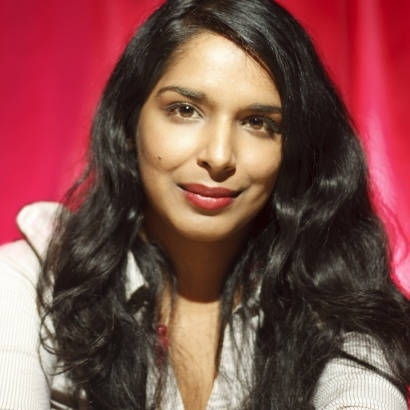 Colour photo of arts journalist & author Anita Sethi against a pillarbox red backdrop