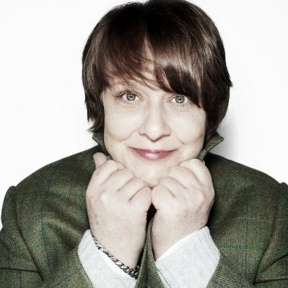 Headshot of Kathy Burke, holding her collar with her hands under her chin