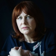 Image of Linda Grant sitting slightly sideways on a chair, with her hands together on the back of the chair