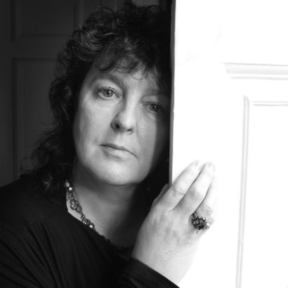 Black and white head and shoulders shot of Carol Ann Duffy, holding on to a white door whilst looking straight ahead