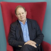 Image of Michael Morpurgo, sitting in a wingback red velvet chair, with his hands on his leg, smiling