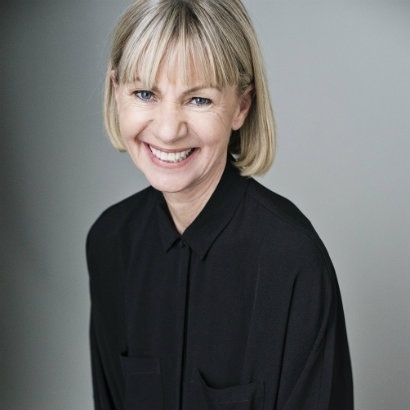 Head and shoulders photo of author Kate Mosse smiling broadly, wearing a black shirt against a grey background