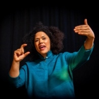 Image of Rommi Smith in front of a dark background, with her hands are in the air gesticulating