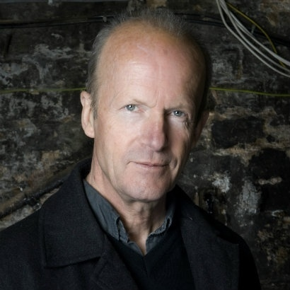 Head shot of author Jim Crace, against a dark stone walll