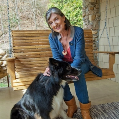 Photo of author Barbara Kingsolver, seated in a chair on a porch, stroking a black and white dog