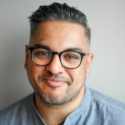 Headshot of author Nikesh Shukla, smiling
