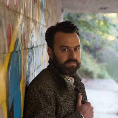 Headshot of author Ben Myers, taken under a canal bridge with graffiti in background