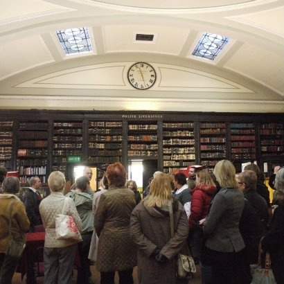 Image of people listening to tour guide in front of bookcases