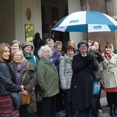 Image of walking tour host, Anne Beswick, surrounded by tour participants, under a large umbrella