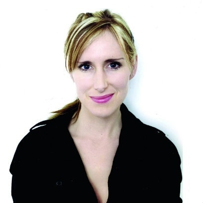 Head shot of children's author and illustrator Lauren Child, wearing a black shirt against a white background, smiling