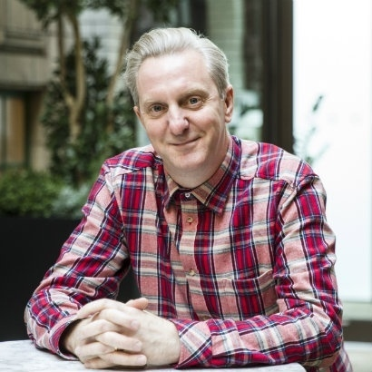 Head and shoulders shot of poet Tony Walsh, wearing a red checked shirt, sitting outside, with his hands interlaced on a table